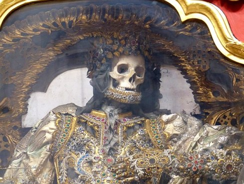 A catacomb saint: a skeleton almost entirely encased in elaborate gold and jewels